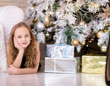 a girl with gifts under the tree